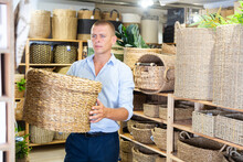 European Man In Shirt Choosing Wicker Basket In Housewares Store.