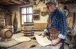 Aged craftsman reads drawings in his rustic wooden barrels producing workshop