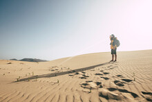 One Man Standing On The Sand Desert Dunes With Backpack Looking Far - Climate Change Arid No Water Future World Earth Concept - Alternative Wild Vacation Lifestyle