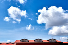 The Fluffy Clouds Floating Over Building Roof