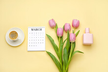Calendar With Cup Of Coffee, Flowers And Perfume On Color Background