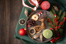 Christmas Or New Year Background, Christmas Tree Decorations And Candles, Dried Fruits And Decorative Deer, Spruce And Cotoneaster Branches On A Green Tablecloth, Top View, Copy Space