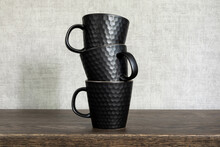 Three Dark Ceramic Tea Or Coffee Mugs Standing On Top Of Each Other. Dark Modern Cups Stacked On A Wooden Background