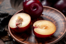 Fresh Sliced Red Plums On A Dark Wooden Background.