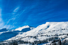 Mountain Peaks Covered With Snow On A Bright Sunny Day Against The Blue Sky. Winter Landscape