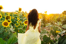 Anonymous Woman In Yellow Dress In Sunflower Field