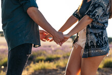 Crop Couple Holding Hands In Countryside Field