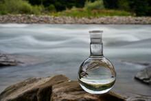 Bottle Of Drinking Water On The Shore Of A Mountain River.