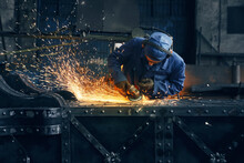 Competent Industrial Worker Dressed In Protective Clothes, Glasses And Gloves Grinding Metal Construction Using Polishing Machine. Sparks From Metal Processing.