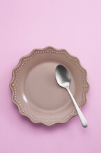 Spoon In Ceramic Dish On Pastel Background