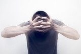 Frustrated and anxious male touching his head against a white background