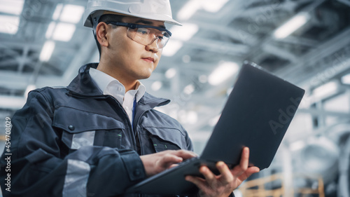 Fotografia Portrait of a Professional Heavy Industry Asian Engineer/Worker Wearing Safety Uniform and Hard Hat Uses Laptop Computer