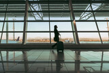 Silhouette of female passenger at airport terminal
