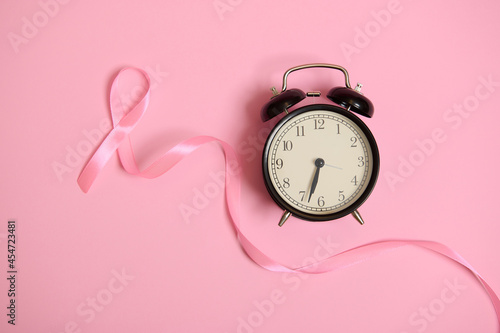 Photo Long pink satin ribbon, where one end is endless and alarm clock on pink background