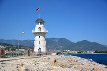 White And Blue Lighthouse On Bank Near Pier With Pedestrian Path And Huge Gray Stones On Sea And Mountain Background