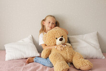 A Little Blonde Girl In A White T-shirt Is Sitting On The Bed And Hugging A Teddy Bear