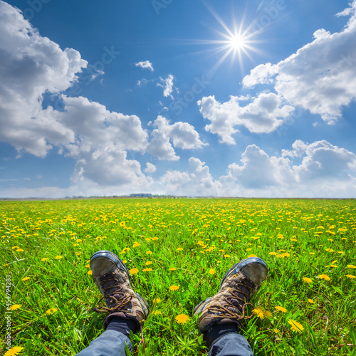 closeup hikers feet in prairie with dandelion flowers, natural travel  background