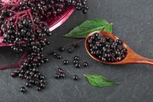 Raw Ripe Elderberry In A Bowl With Green Leaves On A Black Stone Table. European Black Elderberry. Sambucus Nigra.