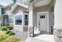 Townhouse Exterior With White Front Door And Bay Windows