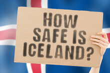 """The Question """" How Safe Is Iceland? """" On A Banner In Men's Hand With Blurred Icelandic Flag On The Background. Safety. Street. Outdoor. Dangerous. Security. Attack. Criminal. Criminality"""