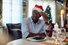 Pensive African American Man Feels Sad While Sitting Alone At Dining Table On Christmas.