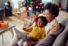 Happy African American Mother And Daughter Greet Someone Via Video Call On Christmas.