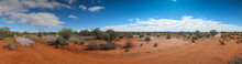Panoramamic View Of The Desert In The Australian Outback After Heavy Rain Showing Large Pools Of Water Under A Blue Sky With Whispy Clouds