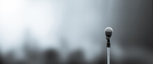 Microphone Public Speaking Background, Close-up The Microphone On Stand For Speaker Speech Presentation Stage Performance With Blur And Bokeh Light Background.