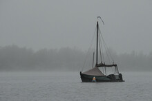 Sailboat On A Lake On A Foggy Morning With Trees In The Background
