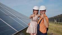A Father, A Solar Power Engineer, And His Daughter Are Standing Near Solar Panels. The Father Explains To The Child The Principle Of Solar Electricity And Puts A Protective Helmet On The Girl's Head.