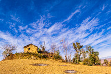 View Of Abandoned Hut Made Of Stones And Mud With Cloudy Blue Sky Background Enroute To Nag Tibba Trekking Trail From Pantwari To Jhandi Peak, Dehradun, Garhwal Region, Uttarakhand, India.