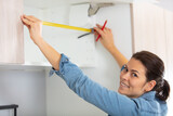 woman remodeling kitchen and measuring wall with tape measure