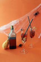 Halloween Drinks, Wine, Pumpkin, Spiders And Mystical Decoration On Bright Orange Background