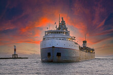 Large Freighter Entering A Holland Michigan Harbor At Sunset Time