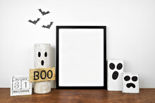 Halloween Mock Up. Black Frame On A Wood Shelf With Rustic Wood Ghost Decor And Calendar. Portrait Frame Against A White Wall With Bats. Copy Space.