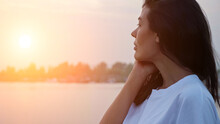 Pretty Brunette Long Haired Woman Touches Cheek With Hand Standing Near Tranquil River At Sunset Time In Summer Evening Close Side View, Sunlight