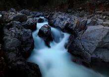 River Cascade Around Large Granite Boulder