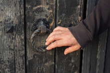Closeup Of The Hand Of A Man Knocking On An Old Wooden Door