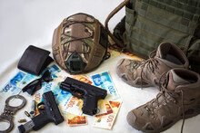 Military Uniform And Equipment, Ammunition. Body Armor, Guns, Bulletproof Helmet, Handcuffs, Sunglasses And Military Boots With Banknotes Of Israeli New Shekels. Weapons For Airsoft And Urban Protests