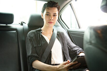 Confident Business Woman With Laptop Computer Sitting On Backseat Of The Car. Female Hand Fastening Seat Belt In Car. Safety First Concept.
