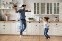 Excited Crazy Dad Teaching Daughter Girl To Dance At Home. Active Funny Daddy And Energetic Kid Exercising Together In Kitchen, Listening To Music, Having Fun, Jumping In Wild Dance, Laughing