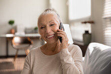 Happy Elderly Lady Talking On Cellphone, Making Call From Home, Speaking To Family On Mobile Phone With Toothy Smile. Senior 70s Woman Consulting Doctor On Cellphone, Chatting To Friend, Laughing