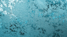 Light Blue Winter Background Or Wallpaper. Drawing Of Ice Crystals And Frost On The Window In Winter. A Pattern Of Leaves Of Fantastic Plants That Look Like Precious Stones. Abstract Backdrop. Macro