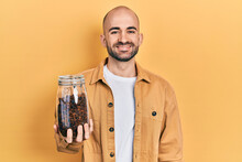 Young Bald Man Holding Jar Of Raisins Looking Positive And Happy Standing And Smiling With A Confident Smile Showing Teeth
