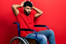 Arab Man With Beard Sitting On Wheelchair Doing Funny Gesture With Finger Over Head As Bull Horns