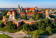 Krakow, Poland. Historic Royal Wawel Castle And Cathedral. Aerial View At Sunset In Summer. Old Town With St. Mary Church In The Background. Park, Promenades And Walking People