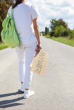 A Beautiful Girl With A Backpack On Her Shoulder Holds A Sign With The Inscription Anywhere. Hitchhiking, Adventure.