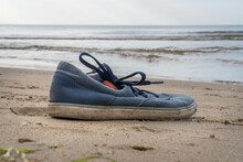 Lonely Tossed Blue, Male Sports Shoes By The Sea.