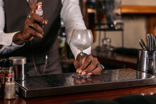 Crop Black Bartender With Cold Glass At Bar Counter