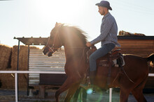 Man Riding Horse In Paddock Against Urban Buildings